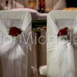 rose rosse e decorazioni sedute sposi