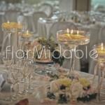 Centrotavola con composizioni floreali e eleganti alzate di vetro con candele