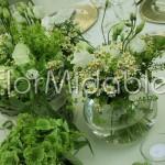 Centrotavola con cesti rustici, fiori verdi e erbe aromatiche