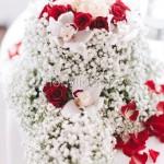 addobbo centrotavola con rose rosse e orchidee su base di velo da sposa