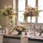 Addobbo tavola elegante con candelabri argento e colori tenui